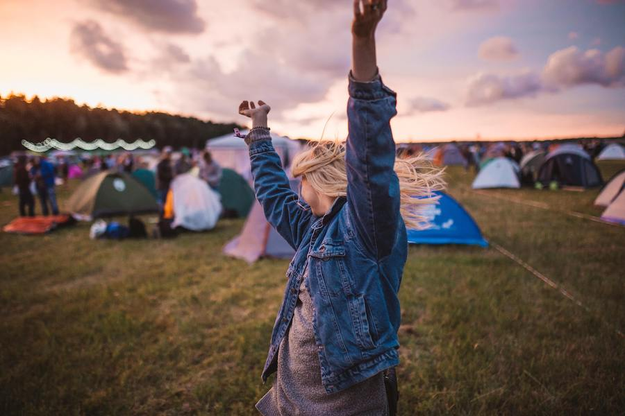 Woman with arms thrown up in the air at sunset in a festival campsite