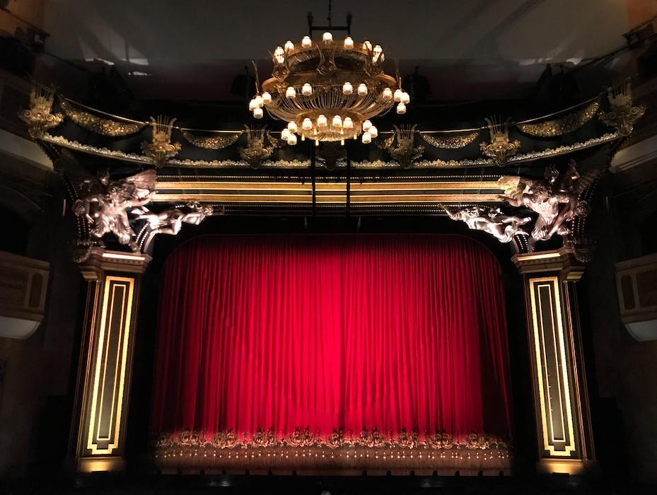 View of theatre stage with traditional red curtain hanging down