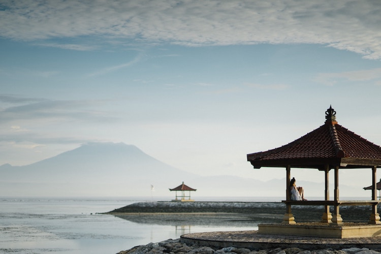 peaceful, open-sided huts dotted throughout calm water with large mountain/volcano in distance