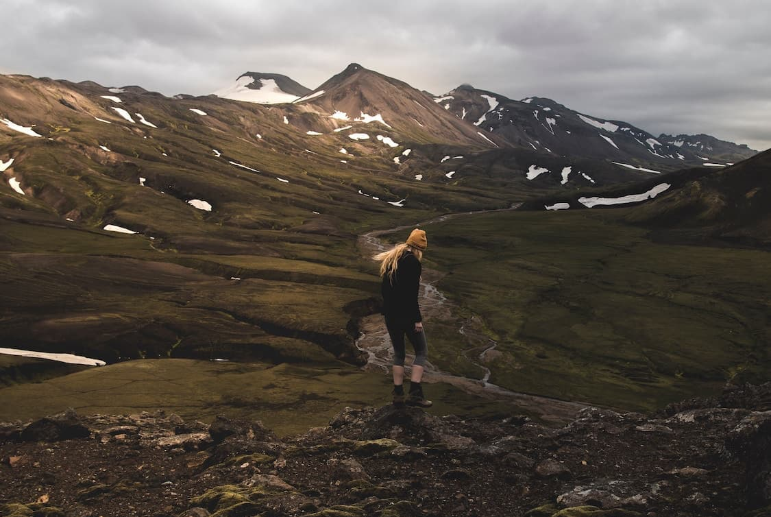 woman standing at top of hill overlooking the mountainous Icelandic landscape