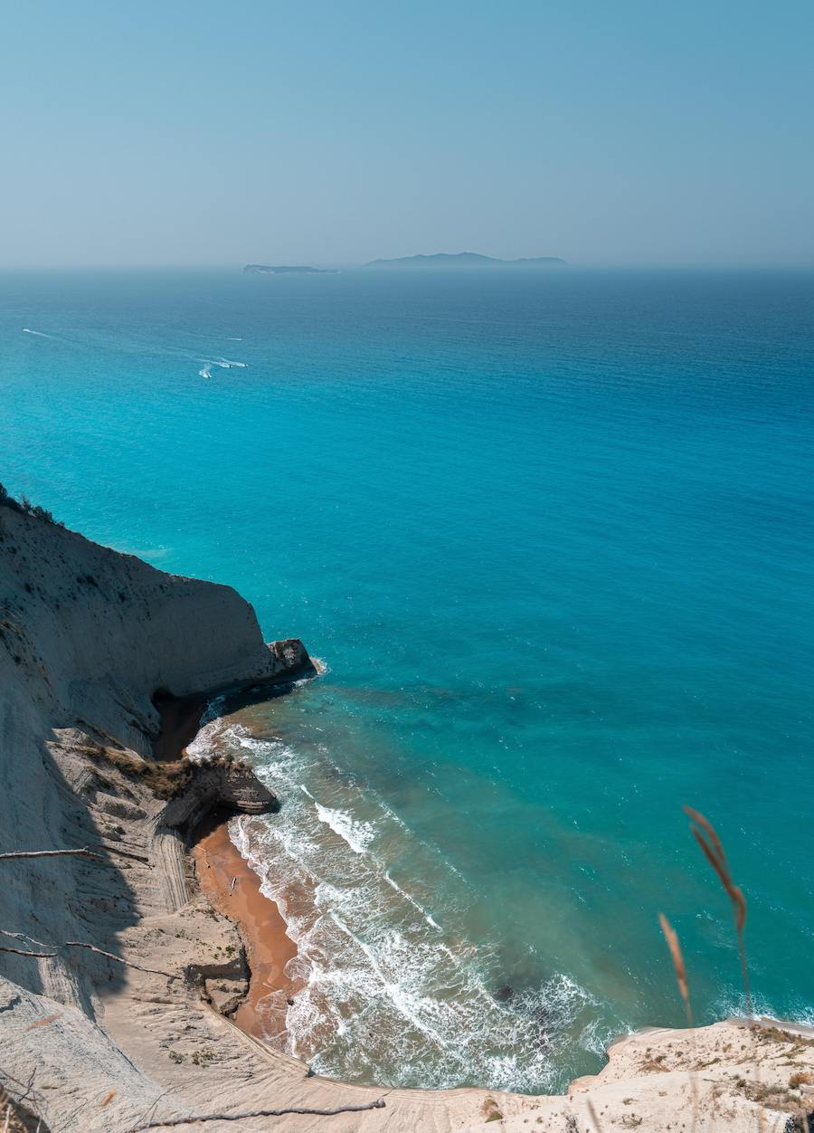 arial shot from cliff-top of island beach with deep, vibrant blue waters