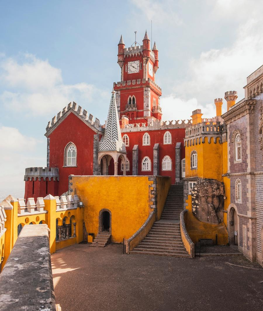 Pena Palace in Portugal — a bright yellow and red painted castle on top of a hill