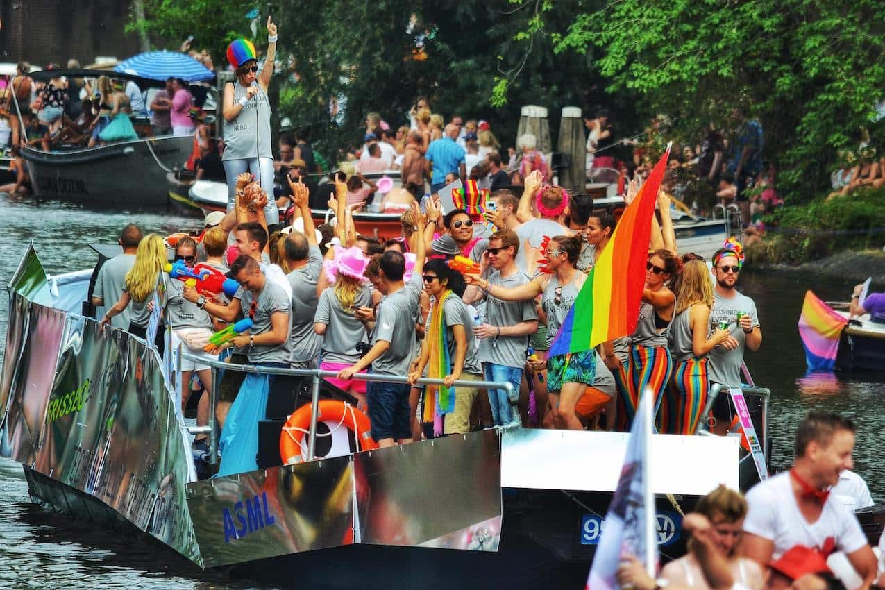 dozens of young people celebrating Gay Pride with rainbow flags and colourful clothes