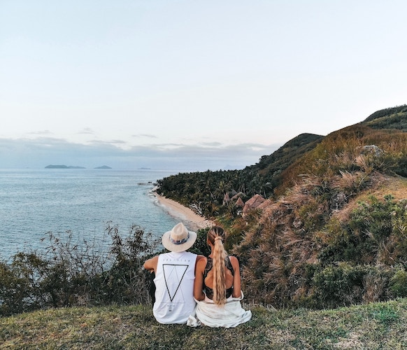 influencer couple overlooking beach from grassy hilltop